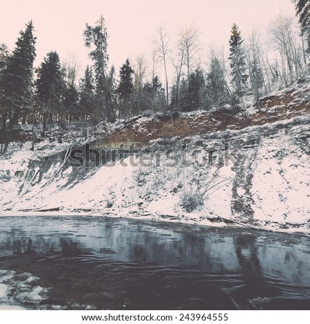 snowy winter river landscape with snow covered trees and blue sky - retro vintage