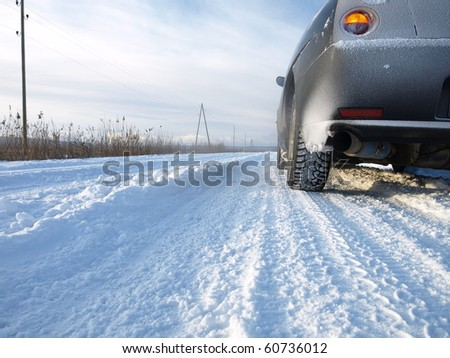 Snowy winter road behind an unrecognizable car - stock photo