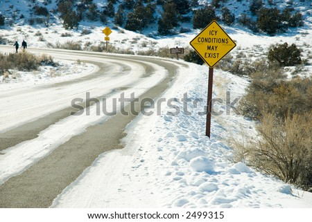 Snowy winter road with icy conditions warning sign - stock photo