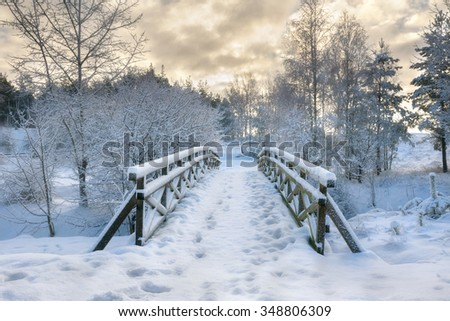 Snowy, wooden bridge in a winter day. Stare Juchy, Poland. - stock photo