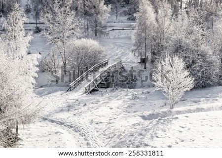 Snowy, wooden bridge in a winter day. View from above. - stock photo
