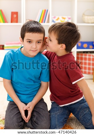 So buddy here is the plan - two kids whispering secrets - stock photo
