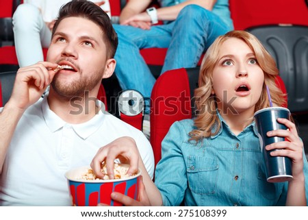 So exciting. Two young people really interested in watching film so they opened their mouths and they eating popcorn and drinking coke - stock photo