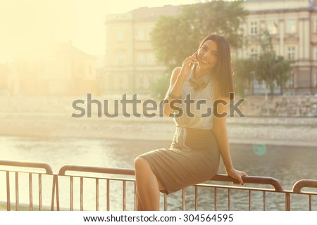 So glad to hear from you! Smiling young woman talking on the phone, enjoying a fun conversation with her friend. Cityscape in the back. - stock photo