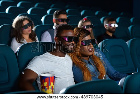 So into this movie. Shot of a young couple looking interested while enjoying a new movie at the local cinema