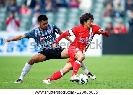 SO KON PO,HONG KONG-FEBRUARY13:Tsuyoshi Yoshitake (R)of HK League Control ball during the Lunar New Year Cup 2013 match between HK League and SCG MTUTD at Hong Kong Stadium on Feb13,2013 in,Hong Kong. - stock photo
