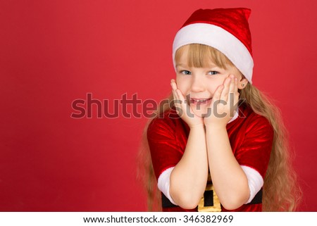 So many presents to come. Studio shot of a little girl wearing Christmas outfit cupping her face in her hands looking excited and smiling cheerfully  - stock photo