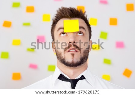 So much work to do! Portrait of frustrated young man in formalwear and adhesive note on his forehead standing against the wall with many adhesive notes on it  - stock photo