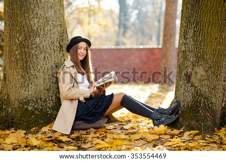 So peaceful here. Soft focus portrait of a pretty girl holding a book smiling resting in the forest - stock photo