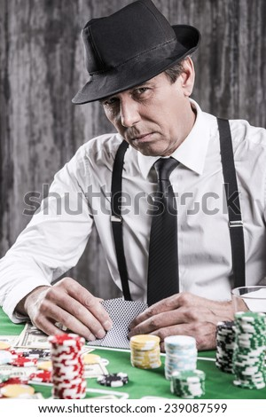 So what you got for me? Serious senior man in shirt and suspenders sitting at the poker table and holding cards  with money and gambling chips laying all around him - stock photo