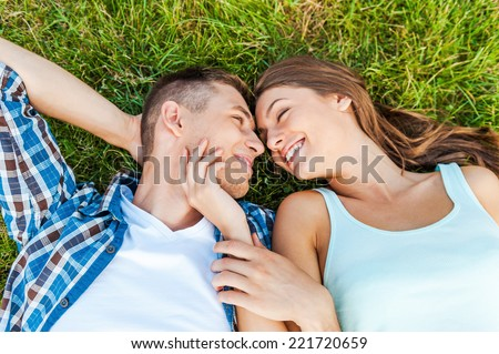 So young and so in love! Top view of young couple sharing their moments lying on the grass in a park - stock photo