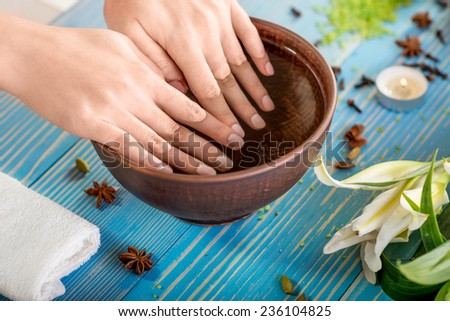 Soaking finger nails in the bath with water on wooden table with spa stuff on background - stock photo
