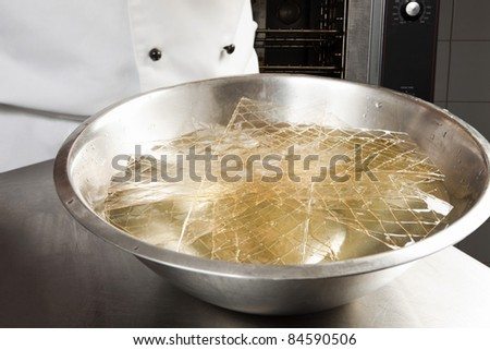 Soaking the gelatin leaves in a bowl of water - stock photo