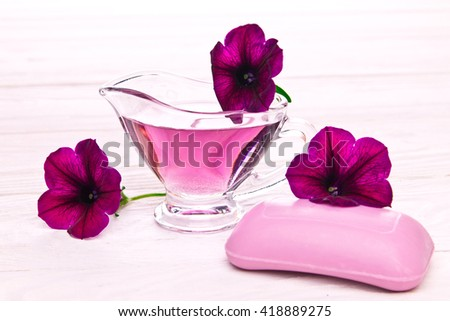 Soap and flower essence on wooden background - stock photo