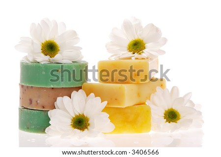 Soap bars and daisies isolated on white