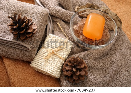Soap, bathing salt and pine cones placed on a towels - stock photo
