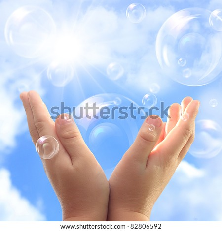 Soap bubbles in child hands against blue sky. - stock photo