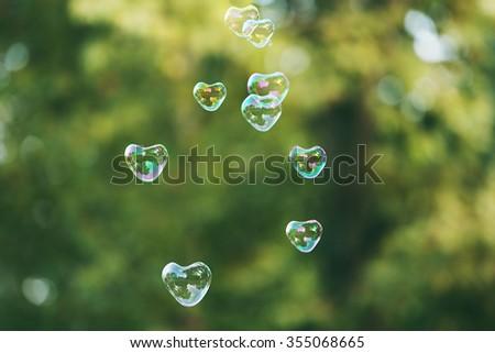 Soap bubbles in heart shape outdoor - stock photo