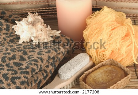 Soap, candle, sponge, sea shells, pumpice brush and leopard towels on bamboo mat - stock photo