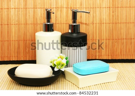 Soap dispensers and bars on bamboo. - stock photo