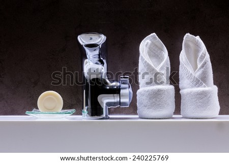 Soap, faucet and towels in the bathroom - stock photo