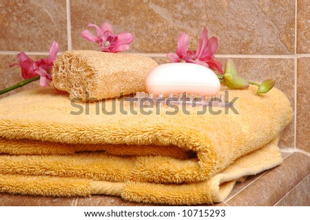 Soap, Loofah and Towel on Tile Spa Bench with Orchids