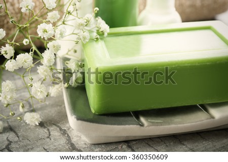Soap on a dish with bottles over wooden background, close up - stock photo