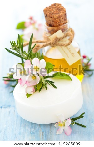 Soap with apple blossom and rosemary on old wooden table. - stock photo