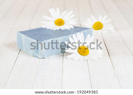 soap with herbal flowers on white wood table