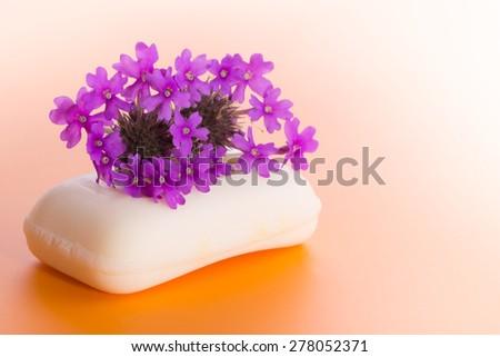 Soap with purple Prairie Verbena flower, on gradient orange background - stock photo
