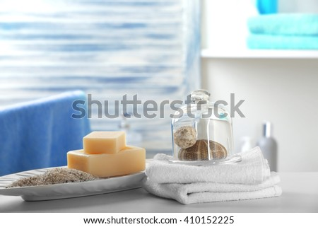 Soap with salt, towels and shells on bathroom table - stock photo