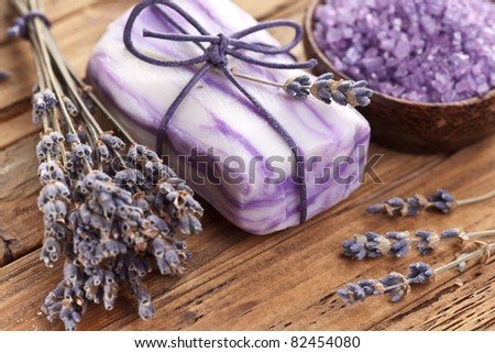 Soap with sea-salt and dried lavender on wood desk. - stock photo