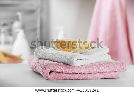 Soap with towels on bathroom table, close up - stock photo
