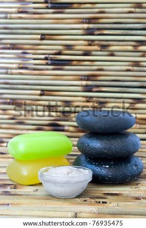 Soaps and facial mask on green bamboo mat