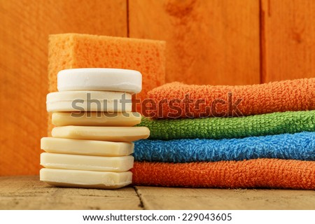 Soaps, towels and sponge shown on the background of stained wood - stock photo