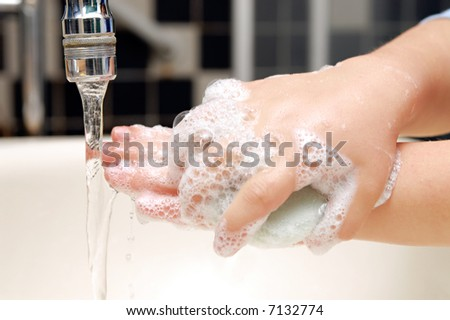 Soapy hands of little child hand-washing in the sink - stock photo