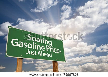 Soaring Gasoline Prices Green Road Sign with Dramatic Clouds, Sun Rays and Sky.