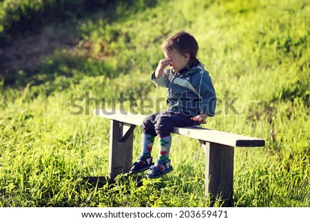 sobbing little boy sitting on a bench in a field - stock photo