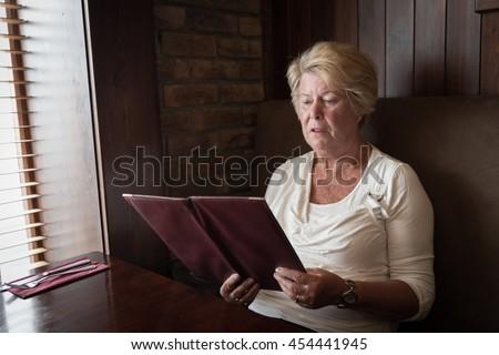 Sober senior woman reading a restaurant menu ready to order food - stock photo