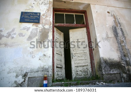 SOBOLI, CROATIA, JULY 31: Commemoration sign and destroyed house as war aftermath. The Croatian War of Independence was fought from 1991 to 1995. - stock photo
