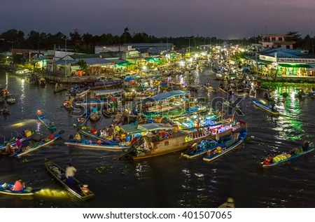 Soc Trang, Vietnam - February 3rd, 2016: Landscape dawn river floating market with busy night boats lights twinkling night agricultural goods to trade in preparation New Year in Soc Trang, Vietnam