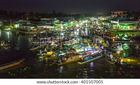 Soc Trang, Vietnam - February 3rd, 2016: Landscape Floating Market at night with bustling boats crossing river in roundabout sales agricultural products prepare welcome New Year in Soc Trang, Vietnam