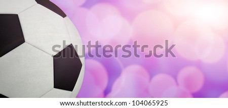 Soccer ball against blurred illumination background. Lot of copy space. Good for sport article or billboard ads or match results. - stock photo
