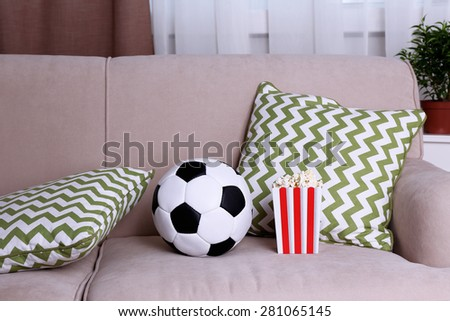Soccer ball and box of popcorn on comfortable sofa, indoors