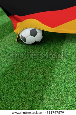 Soccer ball and national flag of Germany lies on the green grass