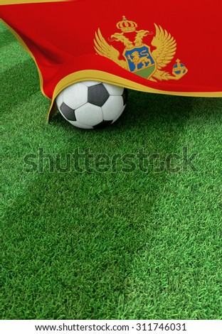 Soccer ball and national flag of Montenegro lies on the green grass