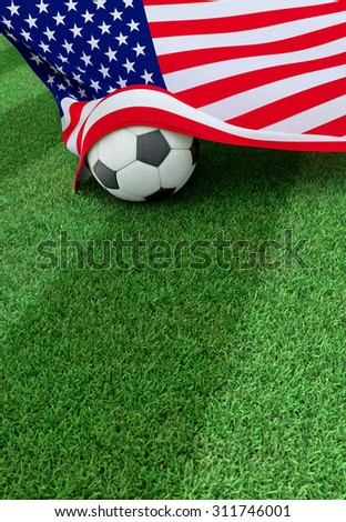 Soccer ball and national flag of USA lies on the green grass