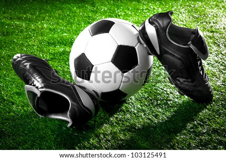 soccer ball and shoes on a green lawn - stock photo
