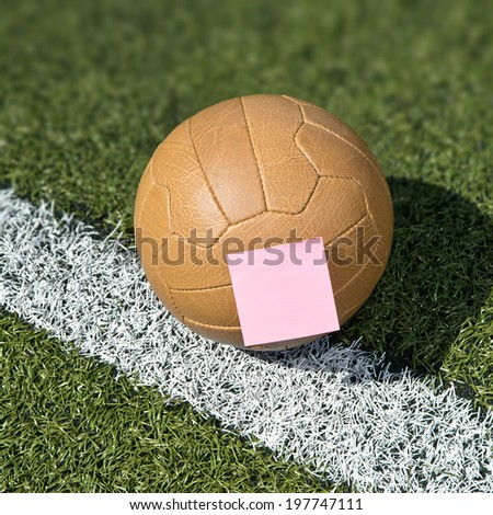 Soccer ball and sticky note - stock photo