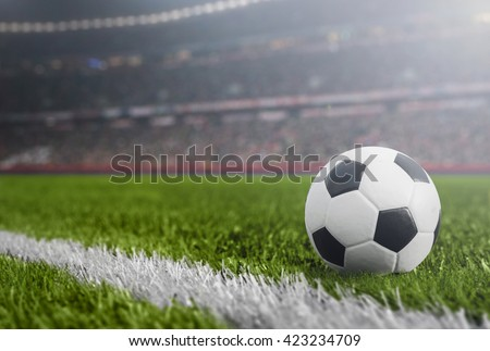 Soccer Ball at night in grass with Stadium and lights in background - stock photo